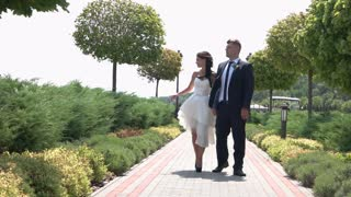 Newlyweds in the park. Bride with groom walking. Discuss plans for nearest future. Happiness built on love.