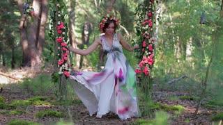 Nice forest fairy on a swing in a gentle chiffon dress.