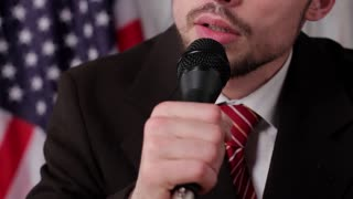 Official man singing into microphone. USA flag behind singer's back. Song dedicated to fellow citizens. Talented man on live TV.