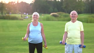 Old couple with dumbbells. People doing physical exercise. Always believe in yourself. Never too late to start.
