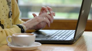 Old hands and laptop. Notebook pc on wooden table. Type a short message.