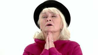 Old lady praying isolated. Senior female with closed eyes.