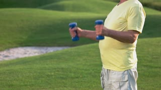Older man with dumbbells. Person does exercise outdoors. Health and strength. Choose path of sport.