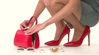 Open handbag and female hands. Legs in red glossy heels. Don't forget perfume and sunglasses. Packed and ready.