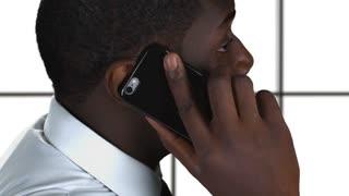 Phone talking on white background. Black guy holding cellphone.