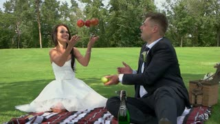 Picnic of a wedding couple. People throwing apples. Our first family picnic. Youth, health and happiness.