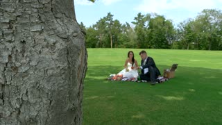 Picnic of the newlyweds. Man and woman on meadow. Humble wedding party. Romance and cheerful mood.