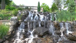 Plants and small waterfall. Water flowing on stones. How to decorate the garden.