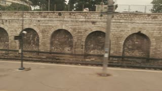 Platform in train window. Old stone wall and railway. Catch up with the schedule.