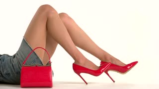 Purse and legs in heels. Red shoes and handbag. How to dress attractive. New collection of elegant footwear.