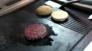 Raw burger patty. Male hand with pepper mill. Quality beef for sandwich.