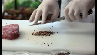 Raw meat piece and spice. Chef cutting black pepper.