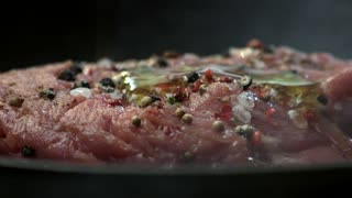 Raw steak and spices. Meat with oil on pan. Cook a dish from beef.