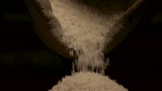 Rice falling from bag. White groats closeup.