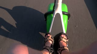 Road and fat wheel scooter. Man's feet in sandals. Fast acceleration and perfect control.
