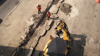 Road workers and excavator. Top view of two men. Renewal of pavement. Must finish work in time.