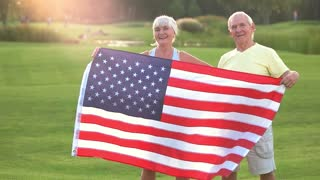 Senior couple holding US flag. Smiling man and woman outdoor. Patriots of strong country. Former olympic champions.