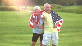 Senior couple holding USA flag. Elderly people show thumb up. Healthy citizens of strong country. Proud to be American.
