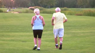 Senior couple is jogging. People running on grass. Health of respiratory system. Do cardio every day.