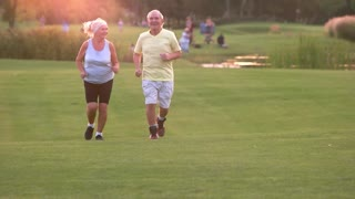 Senior couple running outdoors. Man and woman smiling. Active leisure of pensioners. Save your health.