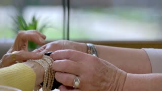 Senior hands with jewelry. Conversation of two women. What is materialism.