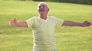Senior man doing exercise. Smiling male outdoor. Stay healthy and strong. Gymnastics in summertime.