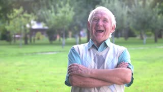 Senior man laughing in slow-mo. Person with crossed arms outdoor. The sense of joke. Wittiness and humor.