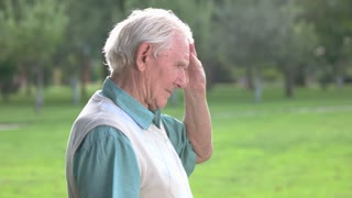 Senior man touches his forehead. Side view of elderly male. You can't rewrite the past. Tired of everything.