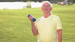 Senior man with dumbbells. Person does exercise outdoor. Be healthy and strong. Work on the muscles.