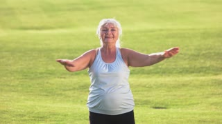Senior woman does exercise. Smiling female on grass background. Gymnastics improves health. Happy and energetic.