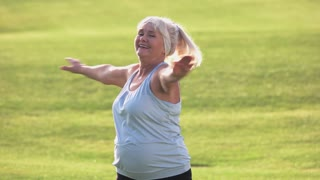 Senior woman doing exercise. Smiling female outdoors. Stay healthy and energetic. Fitness in the open air.