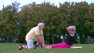 Senior woman doing physical exercise. Couple near trees. Age and strength. Few sets of situps.