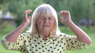 Senior woman holding her head. Upset lady outdoors. Stress causes headaches. Don't know what to do.