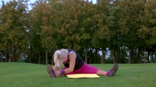 Senior woman stretching. Lady sitting outdoor. Good level of flexibility. End of the workout.