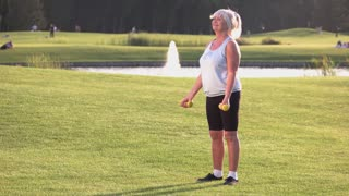 Senior woman with dumbbells. Lady doing exercise outdoor. Workout in fresh air. Curls for biceps.