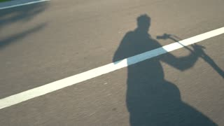 Shadows on asphalt road. Man riding motor scooter. Ride into the summer.