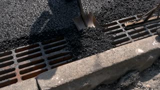 Shovel throwing asphalt. Shadow of a worker. Tar and small stones. Dense layer of durable material.