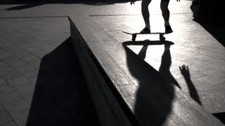 Skateboarder does trick in slow-mo. Feet standing on a skateboard. Pop shove it. Youth chooses sport.