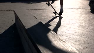 Skateboarder fails a stunt. Feet and skateboard. Try one more time. Stubbornness of the youth.