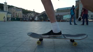 Skateboarder riding on pavement. Side view of skateboard. Ride along the city streets. Youth and freedom.
