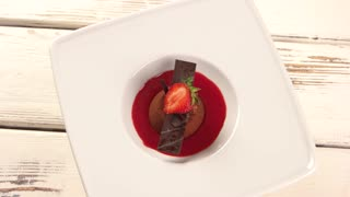 Small chocolate cake with berry. Plate with dessert is rotating.