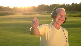Smiling elderly man in headphones. Person with happy face outdoor. In the rhythm of life. Enjoying the art.