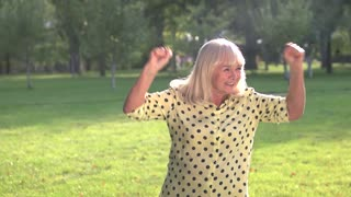Smiling lady with raised fists. Happy senior woman is jumping. Emotions and energy. Winner of the lottery.