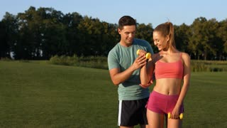Sports trainer engaged in sports with a girl in the park. Sports activities on the nature. Fitness on the street. Healthy lifestyle.