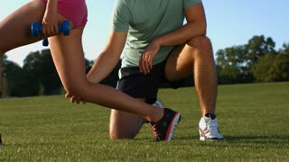 Sports trainer is engaged in fitness with girl outdoors. Fitness on the street. Sports on the nature. Healthy lifestyle.