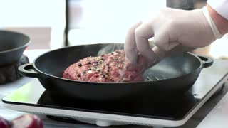 Steak on grill pan. Hand of chef flipping meat. Best recipe of beef.
