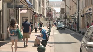 Sunny town street and people. Gift shops and boutiques.