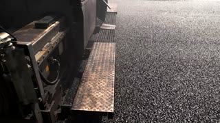 Surface of black asphalt. Back part of road paver. Building roads from best materials. New work plan.