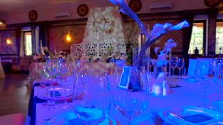 Table with glasses and plates. Interior of restaurant. Wedding banquet in expensive place.
