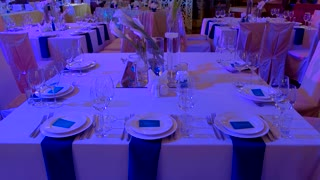 Tables and chairs in restaurant. Wineglasses and empty plates. Perfect place for wedding banquet.